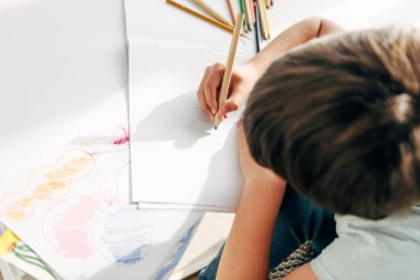 top view of kid with dyslexia drawing with pencil