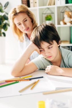 selective focus of sad kid with dyslexia sitting at table and child psychologist looking at him on background