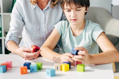 Cropped view of child psychologist and kid with dyslexia playing with building blocks stock vector