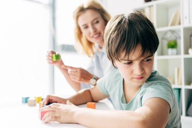 Selective focus of sad kid with dyslexia looking away and child psychologist looking at him and pointing with finger at building block on background stock vector