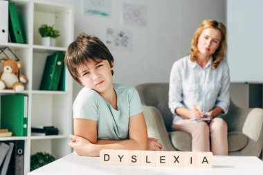 Selective focus of sad kid with dyslexia sitting at table with wooden cubes with lettering dyslexia stock vector