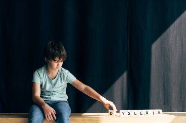 Kid with dyslexia playing with wooden cubes with lettering stock vector