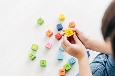 Cropped view of kid with dyslexia playing with colorful building blocks stock vector