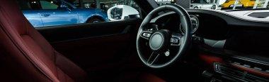 KYIV, UKRAINE - OCTOBER 7, 2019: panoramic shot of car seat near steering wheel in new luxury porshe stock vector