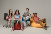smiling friends sitting on different chairs, on grey
