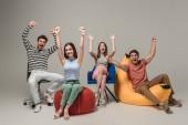 emotionale jubelnde Freunde, die auf verschiedenen Stühlen sitzen, auf grauen