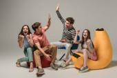 Fotografie aufgeregte Freunde, die HighFive geben, während sie auf verschiedenen Stühlen sitzen, auf grau