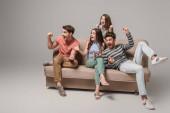 aufgeregte junge Freunde jubeln und sitzen auf dem Sofa auf grau