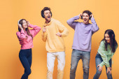 positive friends listening music in headphones and dancing together, isolated on yellow