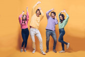 positive friends listening music in headphones and dancing together, on yellow