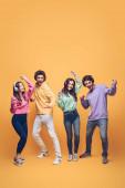 pozitív barátok zenét hallgatni a fejhallgatóban és együtt táncolni, sárga
