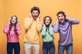 veselí přátelé poslouchají hudbu ve sluchátkách a tančí spolu, izolovaní na žluté