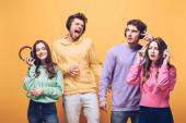 emotivní přátelé poslouchají hudbu ve sluchátkách a tančí spolu, izolovaní na žluté
