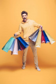 izgatott férfi gazdaság bevásárló táska, sárga
