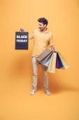 vzrušený muž drží nákupní tašky v černém pátku, na žluté