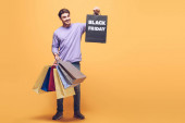 Fotografie usmívající se muž drží nákupní tašky na černý pátek, na žlutou