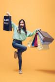 aufgeregte Frau springt und hält Einkaufstüten am schwarzen Freitag, auf gelb