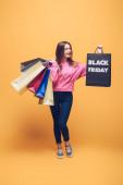 veselá dívka drží nákupní tašky v černém pátku, na žluté