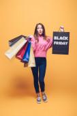 überrascht Mädchen mit Einkaufstüten am schwarzen Freitag, auf gelb