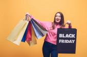 izgatott lány gazdaság bevásárló táskák fekete pénteken, elszigetelt sárga