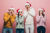 surprised friends in sweaters and santa hats, isolated on pink