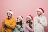 šťastní přátelé ve svetrech a Santa klobouky ukazuje pryč, izolované na růžové