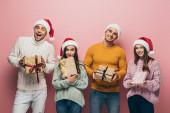 Vidám barátok télapó kalap kezében karácsonyi ajándékok, elszigetelt rózsaszín