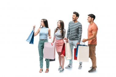 shocked friends walking with shopping bags together, isolated on white