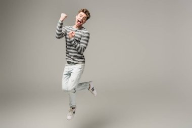 excited screaming man jumping and cheering on grey