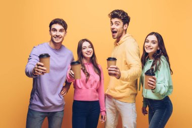 excited friends showing coffee to go, isolated on yellow