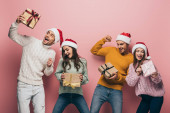 excited friends in santa hats holding christmas presents, isolated on pink