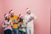 šťastní přátelé v Santa klobouky drží vánoční dárky, izolované na růžové