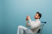 přemýšlivý muž sedící v nákupním košíku, izolovaný na modré