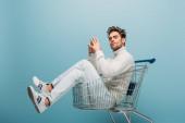 pohledný zamyšlený muž sedící v nákupním košíku, izolovaný na modré