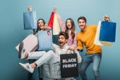 usmívající se přátelé baví s nákupními taškami v nákupním košíku v černý pátek, na modré