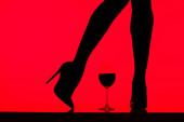 cropped vista di nero silhouette di ragazza in tacchi con vetro di vino isolato su rosso