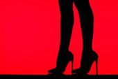 černá silueta svůdné dívky v podpatcích pózující na stole, izolované na červené