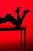 černá silueta vášnivé dívky v podpatky pózovat na stole izolované na červené