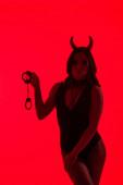 silhouette di ragazza sexy in costume Devil tenuta manette, isolato su rosso