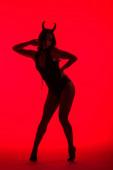silueta vášnivé ženy v kostýmu ďábla, izolovaná na červené
