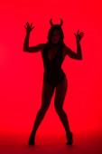 silueta krásné mladé ženy v kostýmu ďábla, izolovaná na červené