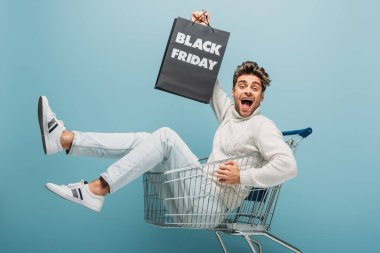 Excited man sitting in shopping cart while holding shopping bag with black friday sign, isolated on blue stock vector