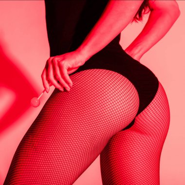 cropped view of sexy buttocks of girl in fishnet tights holding lollipop in red light