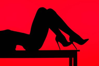 Black silhouette of sexy woman in heels lying on table, isolated on red stock vector