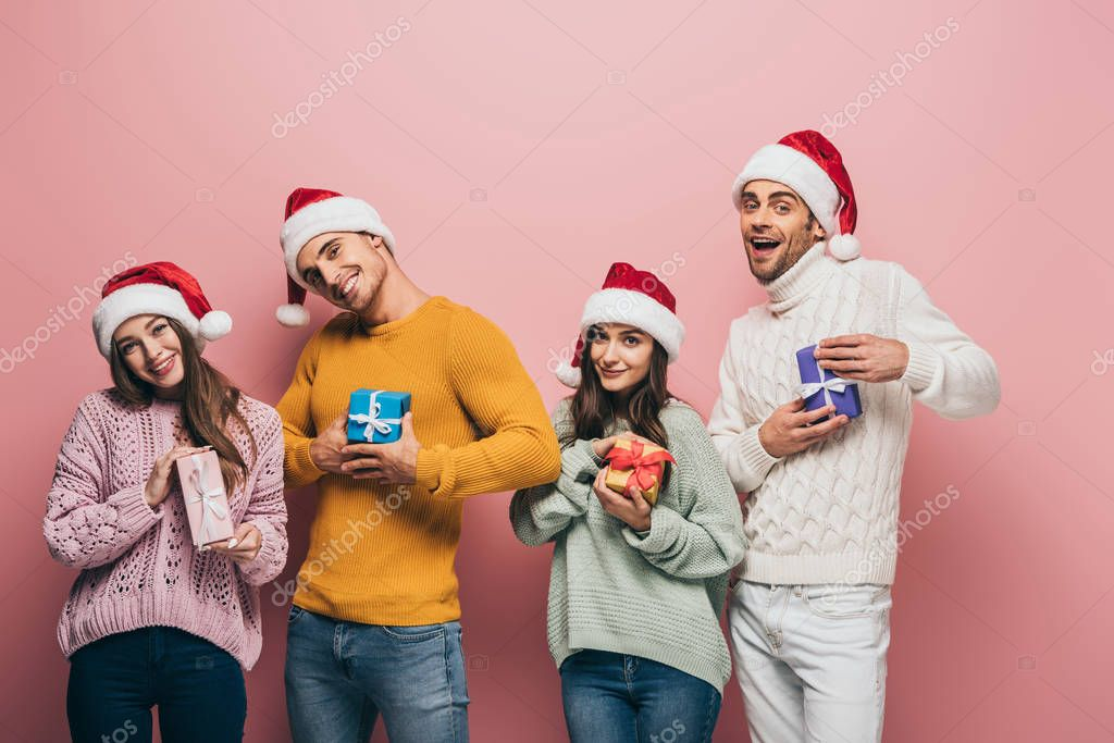 Happy friends in santa hats holding christmas gifts, isolated on pink