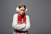 megsértett hideg lány fehér pulóverben, fülvédők és sál pózol keresztbe tett karokkal, elszigetelt szürke