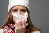 trauriges krankes Mädchen in Strickmütze mit laufender Nase, Papierserviette in der Hand, isoliert auf grau
