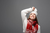 attractive smiling woman in knitted hat and scarf, isolated on grey