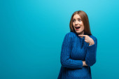 beautiful surprised woman pointing in blue knitted sweater, isolated on blue