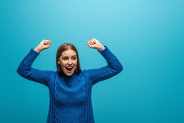 attractive happy woman in blue knitted sweater celebrating success, isolated on blue